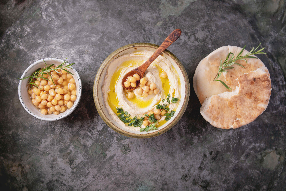 Home made hummus bowl, decorated with boiled chickpeas, herbs, pita and olive oil over a rustic metal background. Top View.